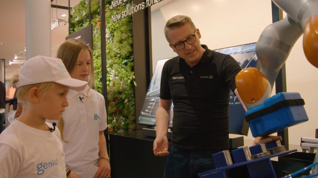 Marc-Oliver Füger, Sprecher der TecFabrik der Daimler AG, erklärt den Genius-Kinderreportern die neue Generation Roboter in der Automobilproduktion.