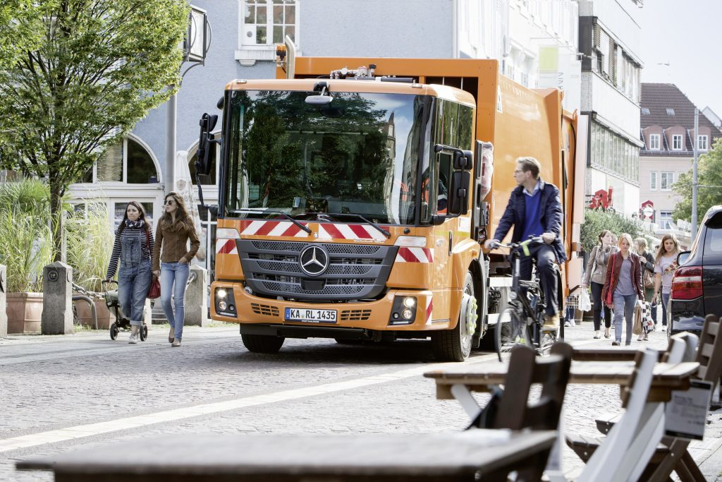 Abbiegeassistent: Ein Müllfahrzeug im Stadtverkehr muss besonders auf Fußgänger und Radfahrer achtgeben. Assistenzsysteme helfen dem Fahrer dabei.