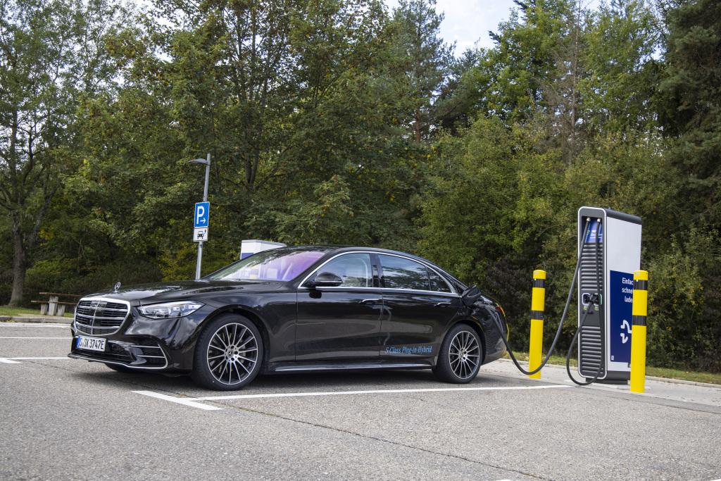 Bild in der Totalen: Eine Mercedes-Benz S-Klasse Plug-in-Hybrid in der Farbe Onyxschwarz steht an einer Ladesäule zum Aufladen