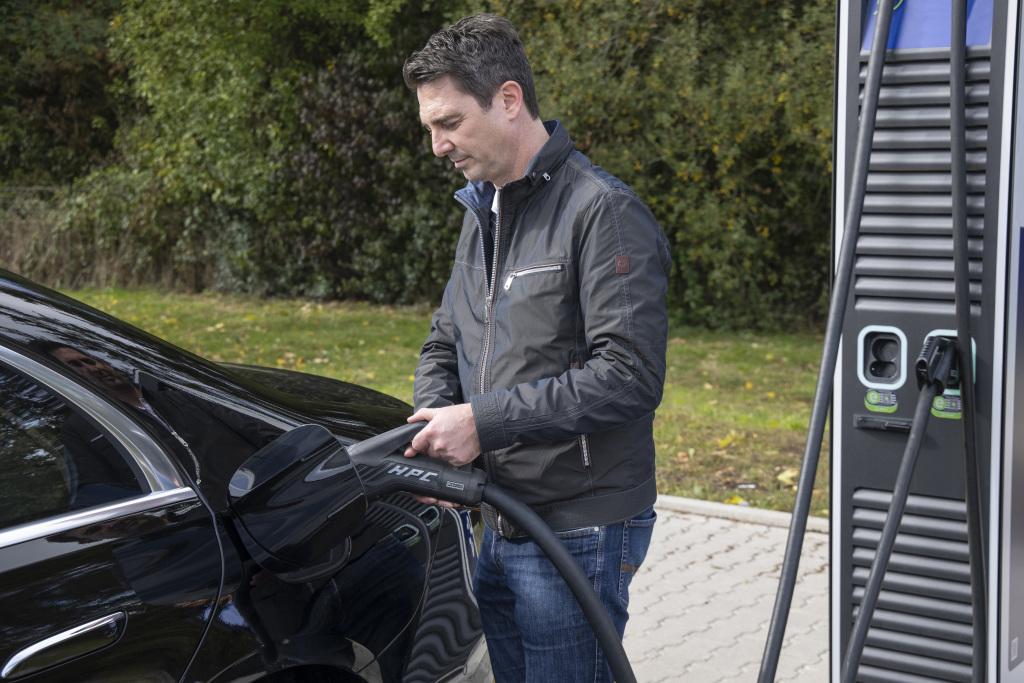 Mann betankt einen Mercedes-Benz-S-Klasse Plugin-Hybrid an einer Ladestation – Genius erklärt Fragen und Antworten rund um die Batterie